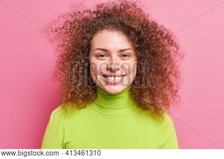 Portrait Of Good Looking Cheerful European Woman With Curly Bushy Hair Smiles Broadly Dressed In Gre