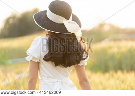 Back View Of Young Woman Wearing Black Hat And White Dress Walking Alone At A Barley Field On A Late