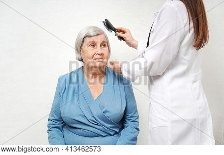 Taking Care For The Elderly. Health Visitor Combing Hair Of Senior Woman In A Nursing Home.