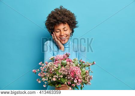 Portrait Of Pleased Curly Haired Young African American Woman Closes Eyes From Pleasure Touches Chee