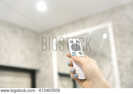 Smart Home Concept With Female Hand Holding A Remote Control