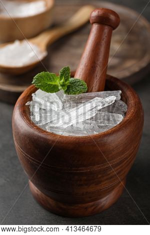 Menthol Crystals And Mint Leaves In Mortar On Grey Background