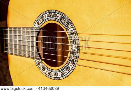 Close-up Of Vibrating Acoustic Guitar Strings. Closeup Shot Of Guitar And Strings With Shallow Depth