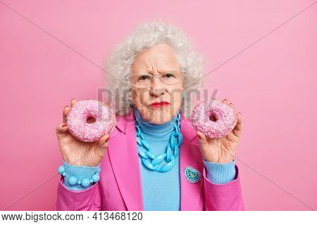 Dissatisfied Wrinkled Senior Woman Holds Two Delicious Doughnuts Eats Junk Food Wears Stylish Outfit