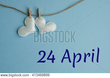 Commemorative Date April 24 On Blue Background With White Hearts With Clothespins, Flat Lay. Holiday