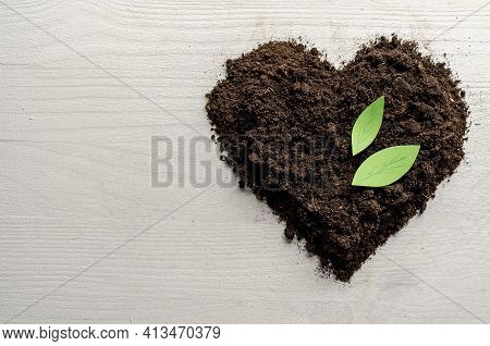 Heart Shaped Dry Soil On White Wooden Background. Earth Day Concept
