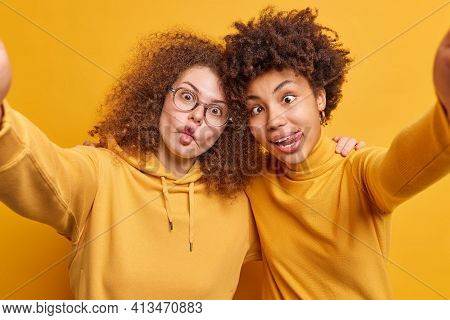 Two Crazy Female Best Friends Make Grimace While Taking Selfie Embrace Spreads Arms Forward Camera H