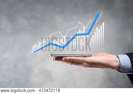 Businessman Holding Graph Growth And Increase Of Chart Positive Indicators In His Business.investmen