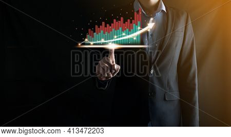 Businessman Holding And Showing A Growing Virtual Hologram Of Statistics, Graph And Chart With Arrow