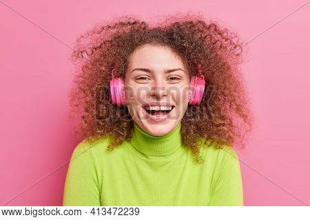 Close Up Shot Of Overjoyed Curly Haired Woman Laughs Out Smiles Broadly Has Curly Bushy Hair Listens