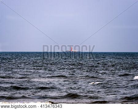 Far Out In The Sea Rises A Lighthouse Emitting Light For Ships.latvia, Cape Kolka, 22 September 2020