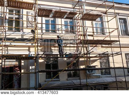 Man Builder Without Construction Helmet Working In Unsafe Way From Scaffolding To Renovate Historic