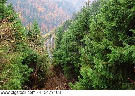 Top View Of The Road Through The Mountain Forest. The High Altitude Makes The Road Look Like A Toy,