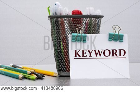 Keyword - Word On A White Sheet With Clips Against The Background Of Cans Of Pencils. Business And E
