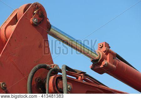 Hydraulic Piston Of A Bulldog-excavator On Blue Sky, With High Pressure Hoses For Hydraulic Fluid. T