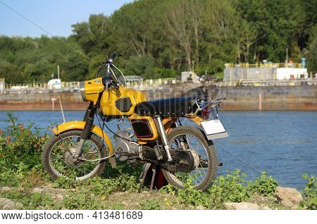 Yellow Old Communist Romanian Motorcycle Near River And Ships .