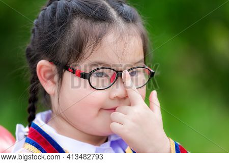 Close Up Of Children Wearing Glasses. Child Pushes The Glasses With His Index Finger To Show Determi