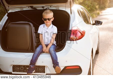 Little Boy Resting On The Side Of The Road On A Road Trip. Road Trip With Children.