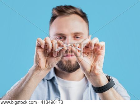 Stop Smoking Concept. Young Bearded Guy Breaking Cigarette On Blue Studio Background, Selective Focu