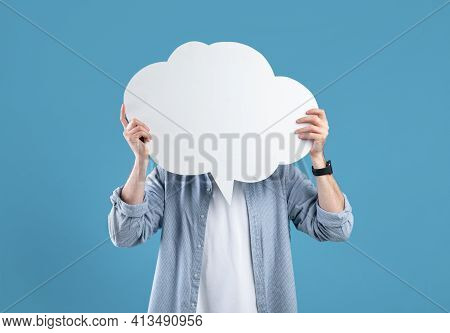 Faceless Young Man Covering His Face With Speech Bubble On Blue Studio Background, Mockup For Design