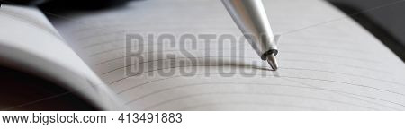 A Metalized Ballpoint Pen Writes In A Lined Notebook. Concept For Creativity, Study Or Office Work,