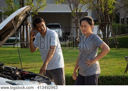 Broken Car Calling For Help On Cell Phone. Broken Car On The Road. Asian Man And Woman Near Broken C