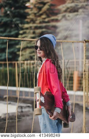 Cute Urban Girl Outdoors With Skateboard. Happy Young Woman With Longboard. Hipster Female In Hat