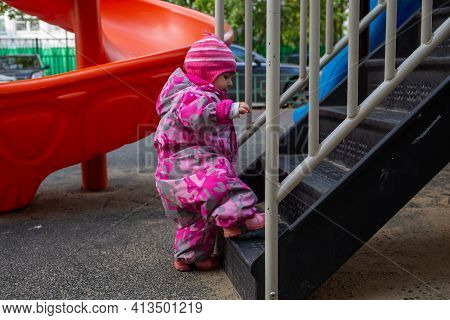 Adorable Toddler Climbs The Stairs On The Playground. Toddler Baby Dressed In Snowsuit. Autumn Or Wi