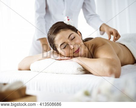 Beautiful Brunette Woman Enjoying Back Massage Comfortable And Blissful. Spa And Medicine Concept