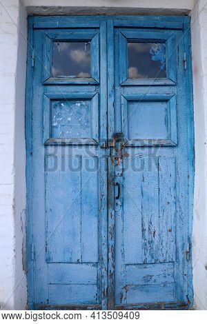 Old Wooden Door With Lock Painted In Blue. Cracked Weathered Wooden Texture.