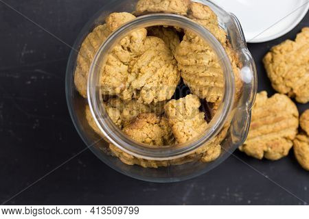Crunchy Cookies In Glass Cookie Jar On Black Table Top Background - Top View Photo With Space For Te