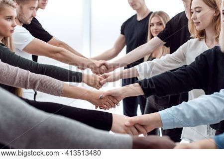 diverse young people shaking hands with each other