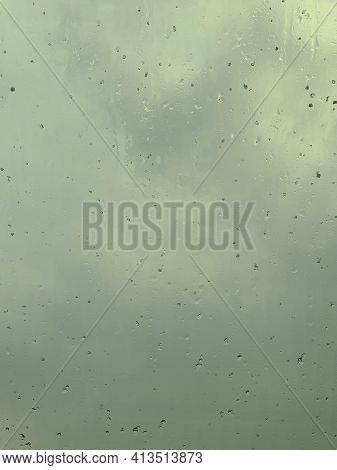Raindrops On The Window During Stormy And Rainy Weather. View Of Dark Clouds Behind The Window.