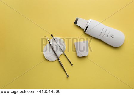 Ultrasonic Scrubber, Uno Spoon Lies On A Yellow Background . Flat Lay, The Concept Of Cosmetology An
