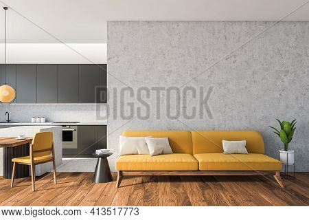 Blank Empty Grey Wall Above Yellow Sofa With Pillows On Parquet Floor. Black Kitchen Interior Set, D