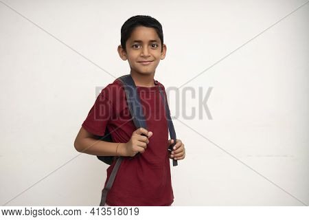 Young Indian Kid Standing On A White Wall With A School Bag On His Back. Getting Ready For School. S