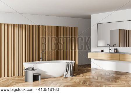 Light Bathing Room With White Bathtub And Sink With Mirrors On Wooden Floor, Table With Towels. Luxu