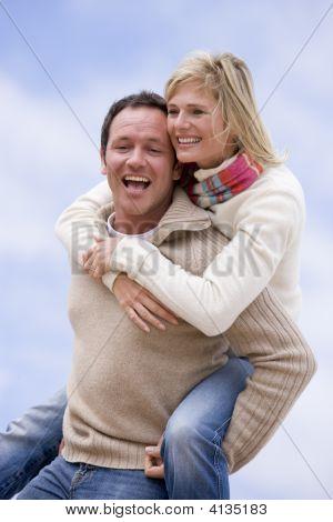 Man Giving Woman Piggyback Ride Outdoors Smiling