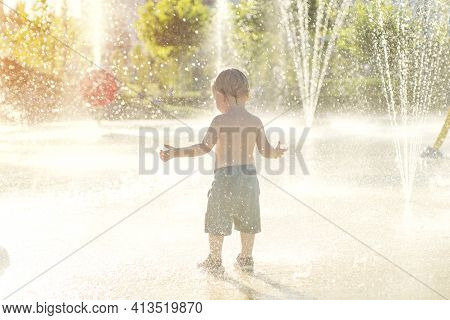 Happy Child Has Fun Playing In Water Fountains On Hot Day During Summer. Boy Playing In Water At Wat