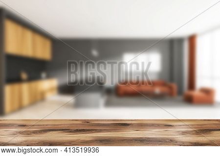 Wooden Desk On Foreground, Blurred Home Interior With Brown Couch And Kitchen Set, Carpet And Window