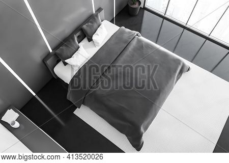 Top View Of Bed With Linens On Dark Floor, Plant In The Corner. Bedroom Interior. Backlight In The W