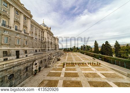 Rear Facade Of The Royal Palace Of Madrid With Its Huge Esplanade And Blue Sky With Clouds At Sunris