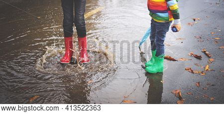 Child Walking In Wellies And Jumping In Puddle On Rainy Weather. Boy Under Rain In Autumn Outdoors