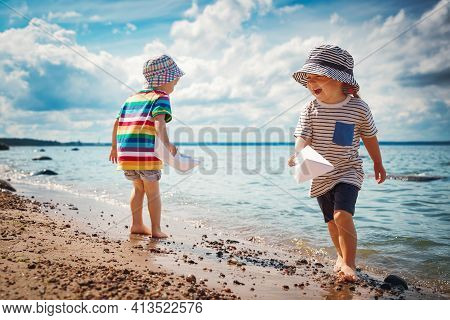 Girl And Boy Playing On The Beach In Summer Hats And Holding Paper Ships. Happy Children Running At