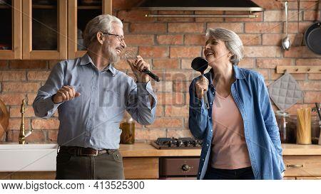 Overjoyed Older Senior Couple Having Fun Sing Songs At Kitchen