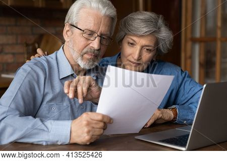 Old Age Married Couple Do Paperwork Engaged In Reading Document