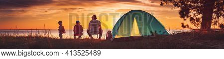 Family Resting With Tent In Nature At Sunset. Man And Children Near Seaside
