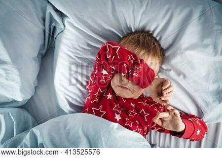 Sleepy Boy Lying In Bed With Blue Beddings. Tired Child In Bedroom. Little Kid Lying Awake In Red Pa