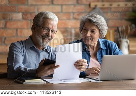 Happy Retired Couple Do Paperwork At Home Office At Kitchen