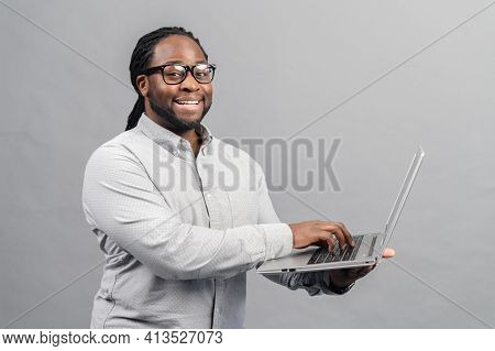 Smiling African Man Using Laptop, Standing At Grey Backdrop, Checking Home Finance, Happy Man Lookin